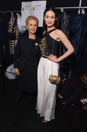 Emmy Rossum attended the Carolina Herrera fashion show carrying an elegant gold chain-strap bag by Christian Louboutin.