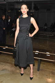 Emmy Rossum made a stylish appearance at the Carolina Herrera fashion show in a black-and-white striped midi dress from the brand.