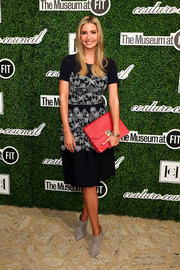 Ivanka Trump injected some color into her monochrome outfit with an oversized red leather clutch.