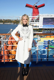 Carrie Underwood visited the Carnival Vista cruise ship wearing a white coat with a studded front.