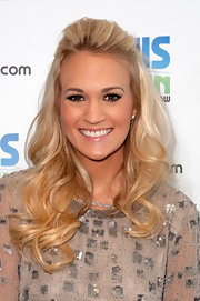Carrie Underwood swept back her bangs and wore her longer lengths in flowing curls while on the Z100 Elvis Duran morning radio show.