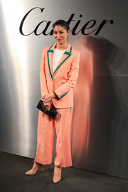 Caroline Issa attended the Santos de Cartier watch launch looking bright in a peach Racil suit with green trim.