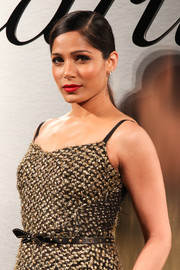 Freida Pinto styled her metallic dress with a studded black belt by Gucci for the Santos de Cartier watch launch.