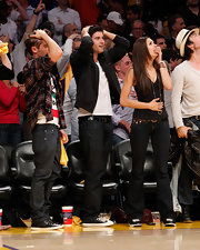 Nina sat courtside in black sneakers and dark jeans with top-stitching and flap pockets.