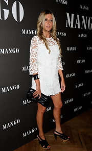 Natalie Alvarez paired her white lace dress with a cool leather clutch.