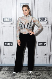 Ashley Graham flashed her black bra in a white laser-cut top by Beaufille while visiting Build.