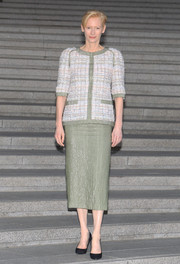 Tilda Swinton attended the Chanel Cruise show wearing a tweed jacket and a matching pencil skirt from the French fashion house's Spring 2015 Couture collection.