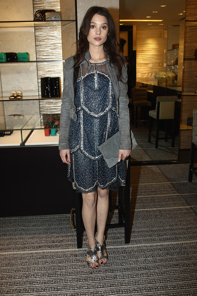 Astrid Berges Frisbey accessorized with a scalloped gray suede clutch that matched her jacket perfectly.