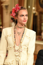 Cara Delevingne accessorized her suit with layers of pearls for the Chanel Collection des Métiers d'Art show.