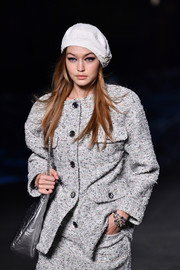 Gigi Hadid looked cosmopolitan wearing a white beret with a gray tweed outfit on the Chanel Cruise runway.