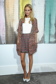 Poppy Delevingne looked mildly retro in a colorful knitted skirt suit during the Chanel fashion show.