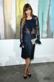 Lou Doillon paired a sheer blue ruffle blouse with an elegant pencil skirt for the Chanel fashion show.
