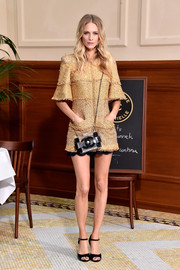 Poppy Delevingne put on a leggy display at the Chanel show in a gold tweed mini dress from the brand.
