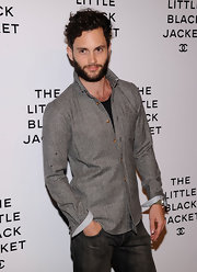 Penn Badgley struck a pose at Chanel's: The Little Black Event in a gray fitted jacket.