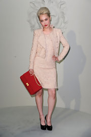 Rinko paired her tweed skirt suit with a bright red shoulder bag.