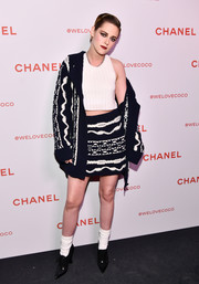 Kristen Stewart bundled up in an oversized black-and-white cardigan by Chanel for the brand's Beauty House celebration.