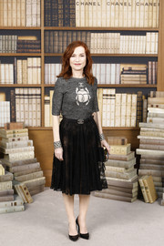 Isabelle Huppert added a touch of sexiness with a sheer black lace skirt.