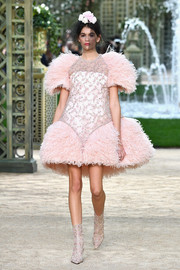 Kaia Gerber showed off an intricately embellished pink cocktail dress with a feathered skirt and sleeves at the Chanel Couture runway show.