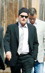 Charlie Sheen kept his head warm in a black beanie, a strange pairing with a formal suit.