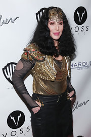 Cher looked theatrical in a cropped gold vest layered over a draped chainmail blouse and a mesh top at the Marquee Club in NYC.