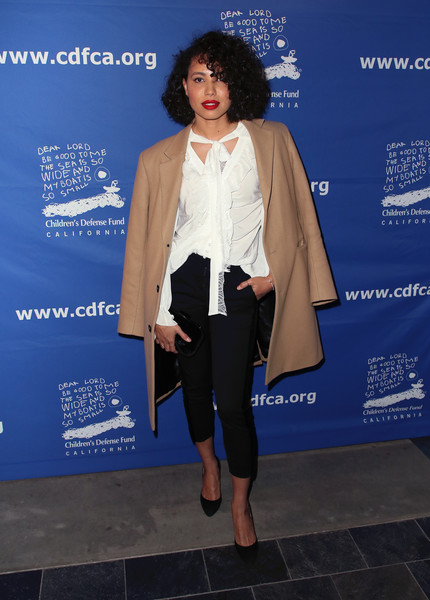 Underneath her coat, Jurnee Smollett-Bell wore a white tie-neck blouse with ruffle detailing.