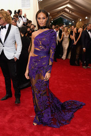 Joan Smalls brought major allure to the Met Gala red carpet with this see-through purple one-shoulder gown by Roberto Cavalli.