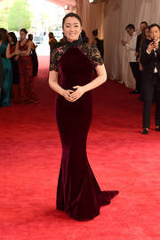 Gong Li totally got into the Met Gala theme in a floor-sweeping burgundy velvet cheongsam with black lace sleeves, designed by Roberto Cavalli.