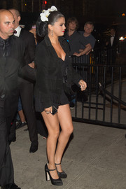 Selena Gomez arrived for a Met Gala after-party wearing a fringed black suede jacket over a romper.