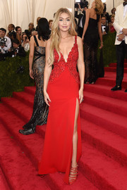 Gigi Hadid flaunted her enviable model figure in a plunging, high-slit red gown by Diane von Furstenberg during the Met Gala.