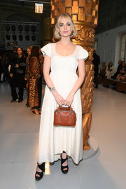 A stylish brown leather purse rounded out Lucy Boynton's ensemble.