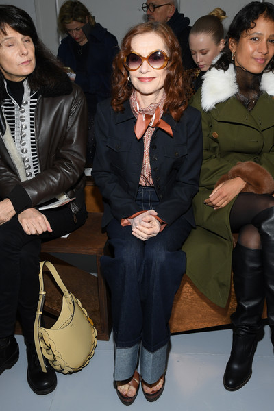 Isabelle Huppert sat front row at the Chloe Fall 2020 show wearing a navy military jacket from the brand.