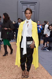 A lemon-yellow duster coat added an exuberant pop to Jada Pinkett Smith's monochrome look.