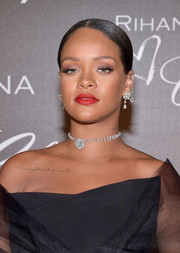 Rihanna swiped on some red lipstick for a splash of color to her black outfit.