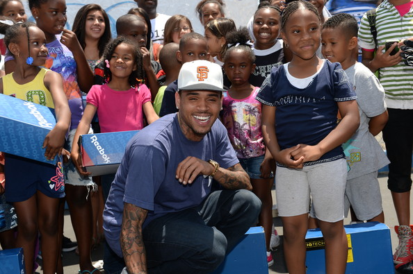 Chris Brown protected himself against the harsh Los Angeles sun by donning a white baseball cap as he flashed a big smile for the kids of Crenshaw Senior High School.