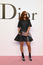 Rihanna styled her cute dress with a pair of printed mid-calf boots, also by Dior.