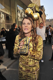 Never to be outdone, Anna dello Russo attended Paris Fashion Week with a gold apple head piece and matching metallic ensemble.