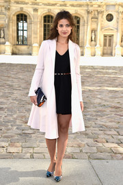Esther Garrel layered a white A-line coat over an LBD for the Christian Dior fashion show.