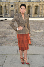 Sirivannavari Nariratana opted for a houndstooth skirt suit, featuring a tan jacket and a contrasting orange pencil skirt, for the Dior fashion show.