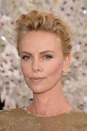 Charlize Theron swept her wavy locks back into a loose updo for the Christian Dior Couture fashion show.