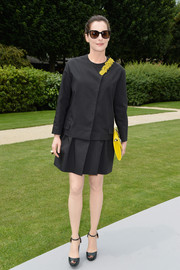 Amira Casar kept it minimal in a loose black top with yellow flower accents during the Dior Couture fashion show.
