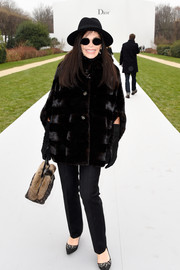 Mouna Ayoub glammed it up in a black fur coat during the Dior Couture show.