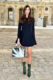 Christina Pitanguy donned a navy mini dress with pleated peplum detailing for the Christian Dior fashion show.
