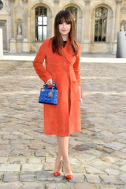 Miroslava Duma accessorized with a blue Dior satin purse that contrasted beautifully with her orange outfit.