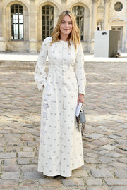Camille Rowe attended the Christian Dior fashion show all covered up in a white floor-length coat from the label.
