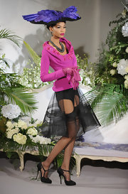 Chanel is wearing a silk garter belt with stockings and a peek a boo over skirt. This is a modern take on an otherwise traditional look. The most interesting item in this look is her shoes. They are black satin with small hooks. They are inspired by the garter belt and pull this entire ensemble together nicely.