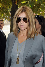 This gold chain and pendant adds personality to Carine's grey business attire.