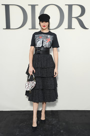 Shailene Woodley teamed her outfit with a printed purse by Dior.
