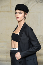 Cara Delevingne layered a black bandeau bra under a tailored jacket for the Dior Fall 2018 show.