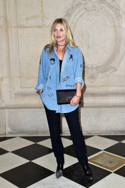 Kate Moss went rugged in an Elvis-themed denim shirt, which she wore unbuttoned over a black top, during the Dior fashion show.