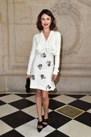 Olga Kurylenko cut an ultra-feminine figure in an embellished white ruffle dress by Christian Dior during the label's fashion show.